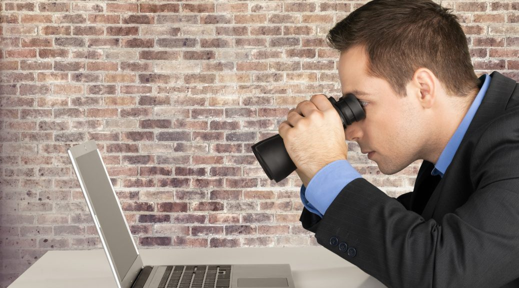 man using binoculars to view laptop