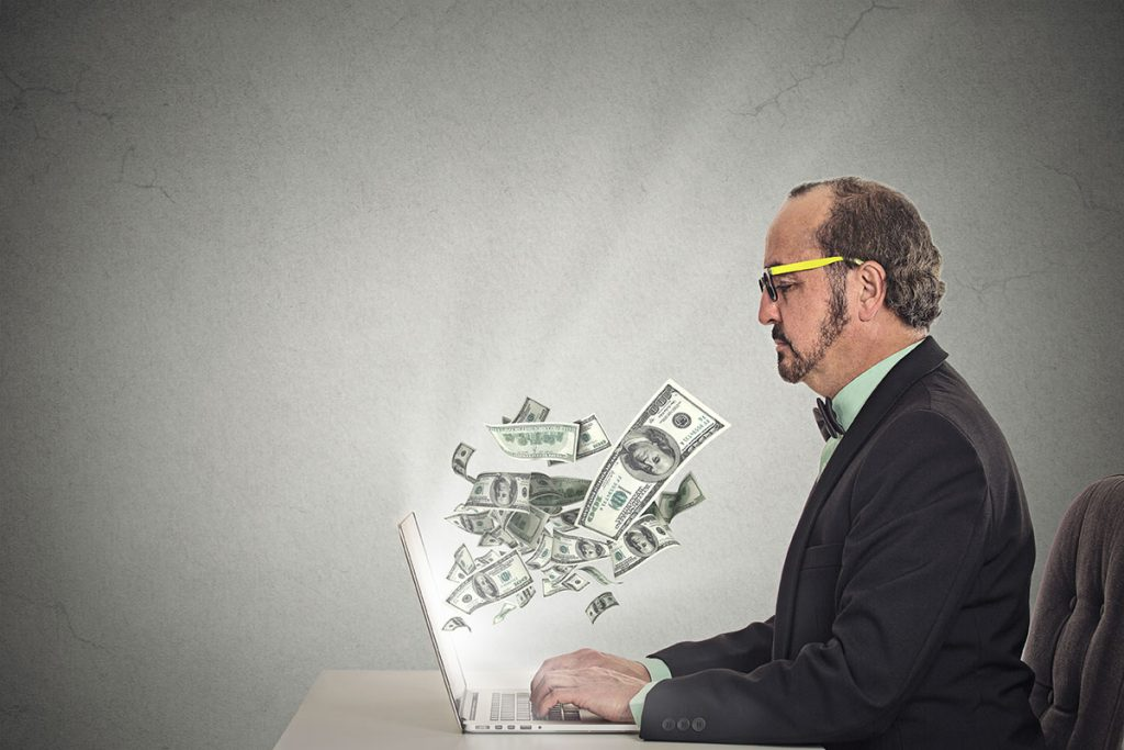 man with money flying out of his laptop