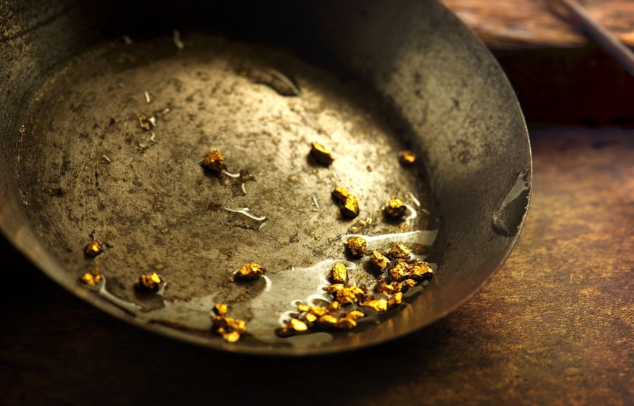 pan with gold nuggets implying gold rush