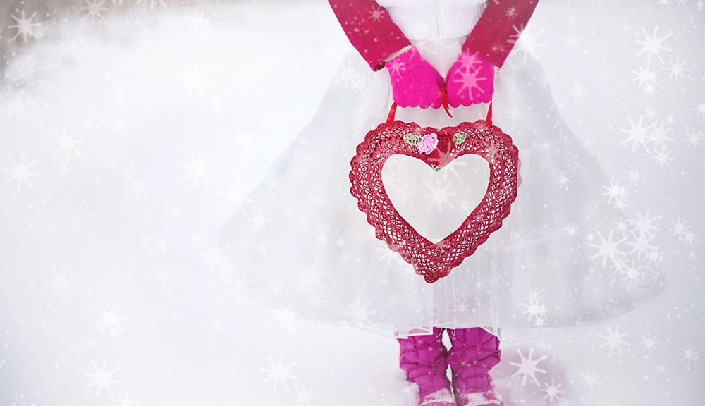 girl holding heart purse in snow