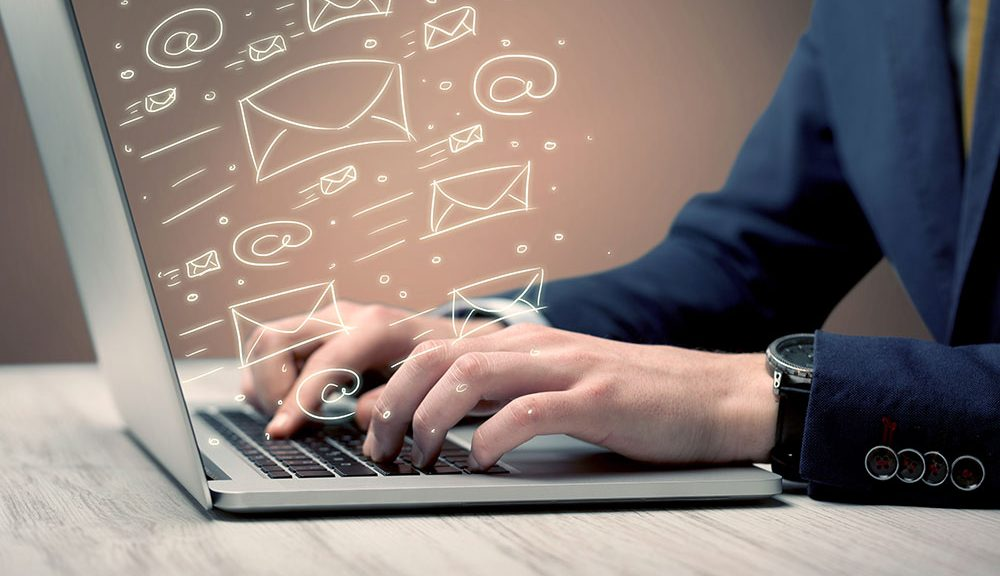 person sending email on laptop