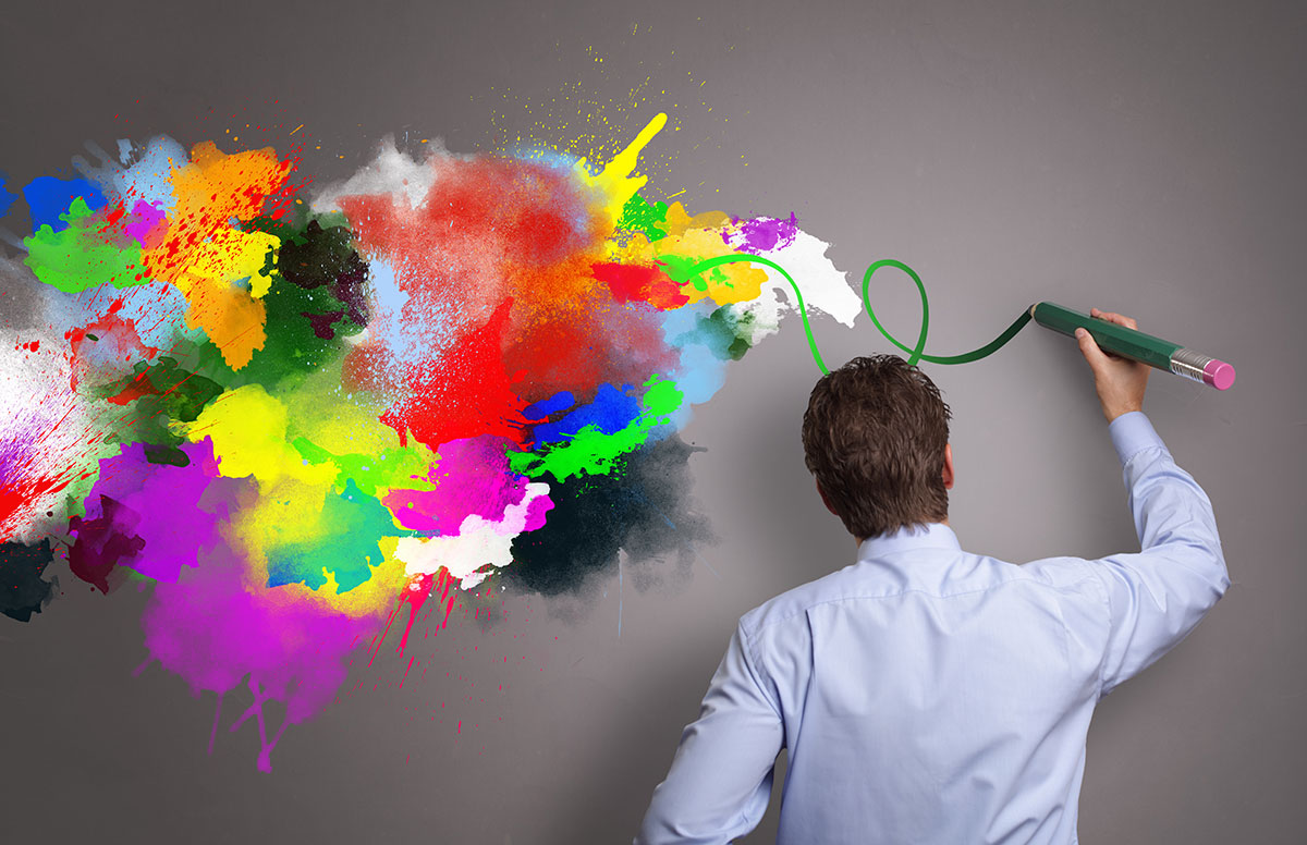 man painting colorful design on wall