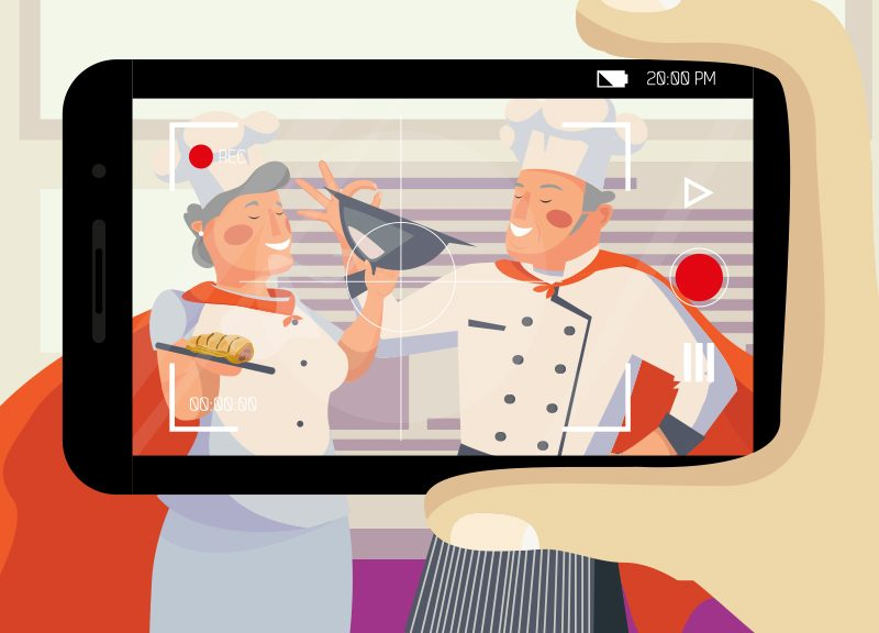 Image of someone recording two chefs doing a cooking vlog