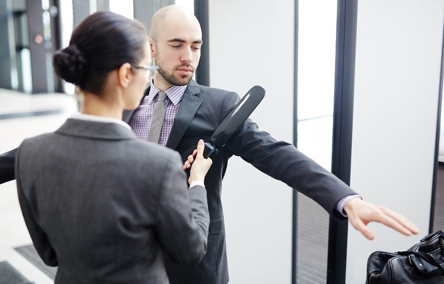 Airport security checking one of passengers with metal detector