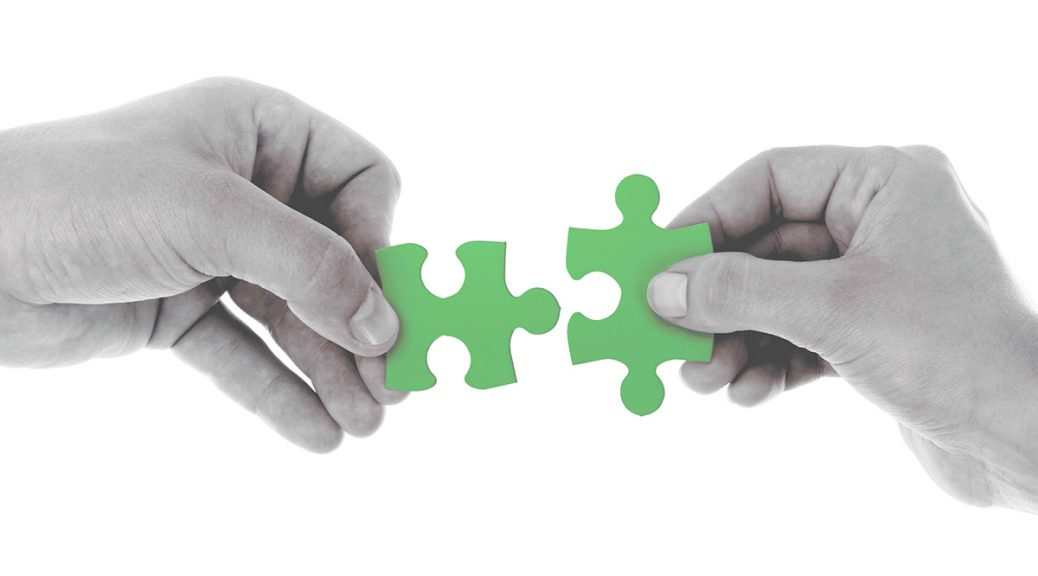 hands putting together puzzle pieces