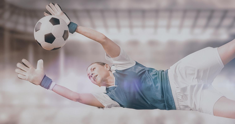 female goalie stopping a soccer ball