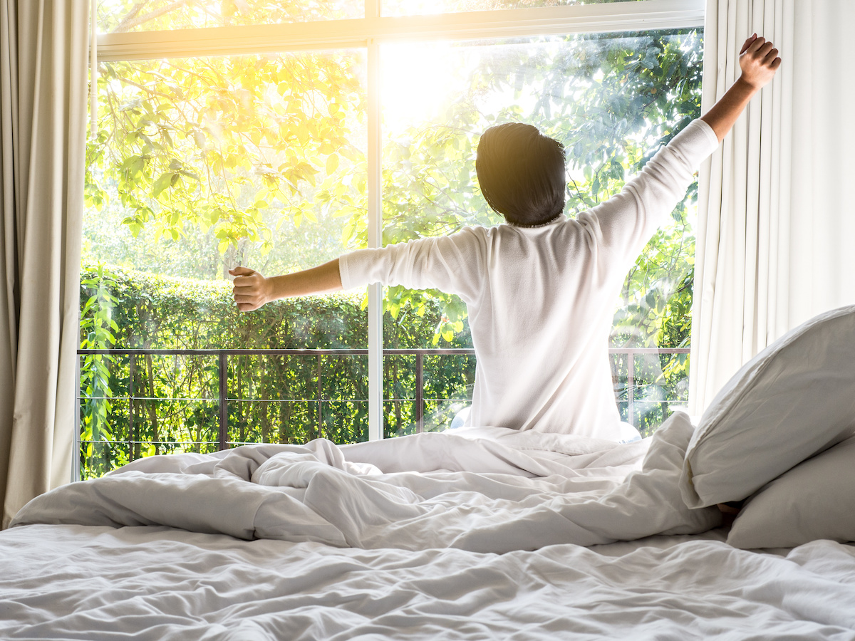 Man waking up refreshed and happy